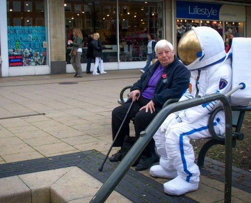 Sitting on and boy in astronaut costume.