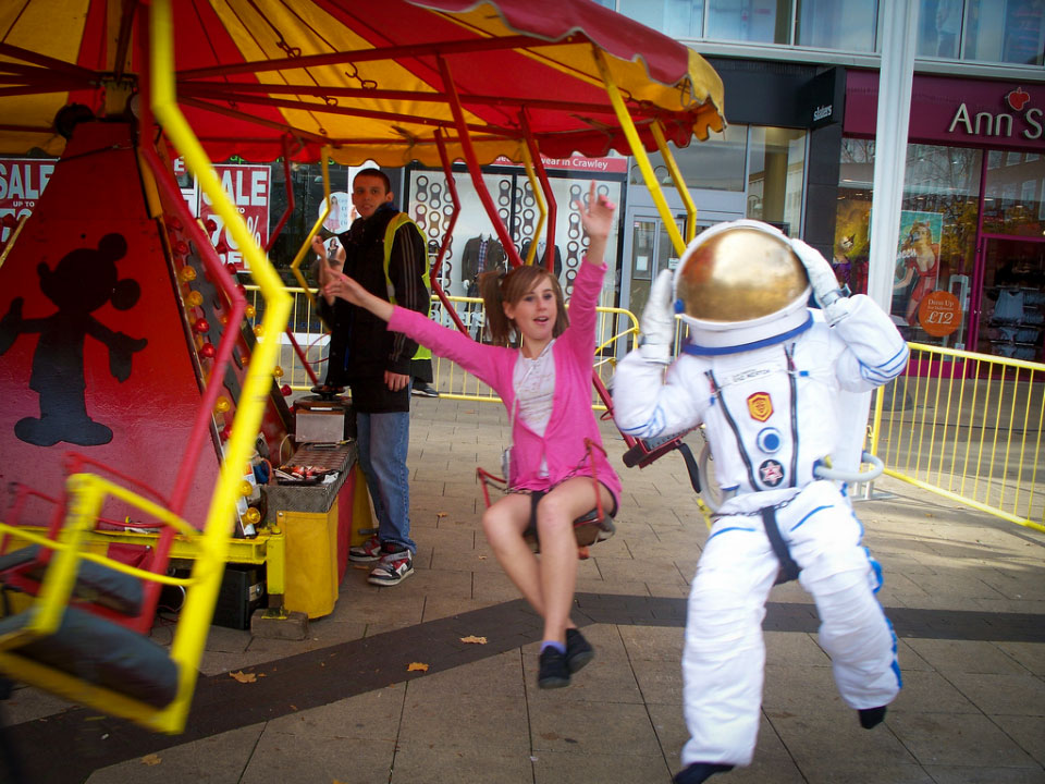 Astronaut and girl on merry-go-round.