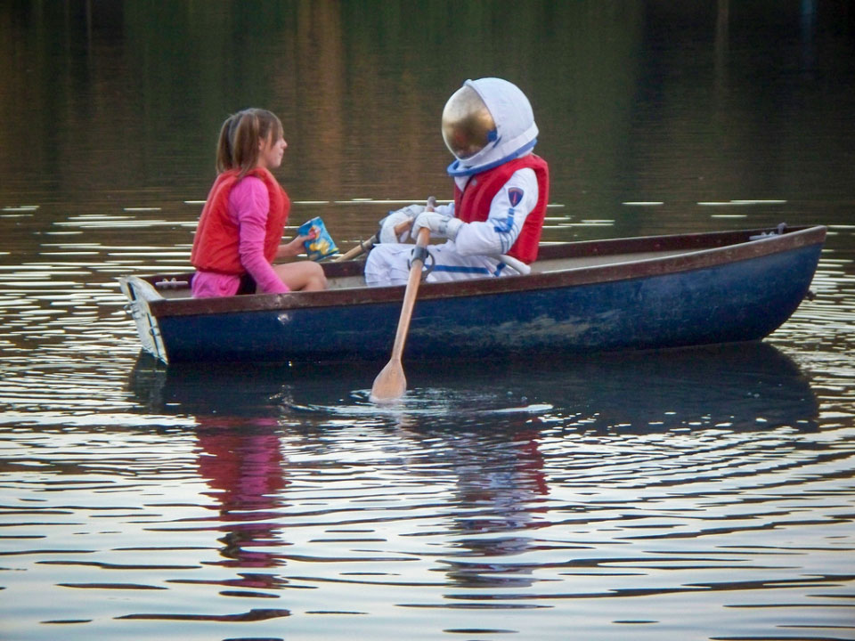 Astronaut boy and girl in boat.