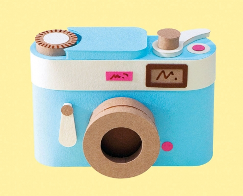 Vintage camera paper art on yellow background.